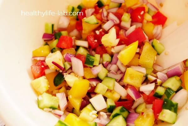 夏野菜と茹でたもち麦を混ぜ合わせ、ドレッシングで和えた写真